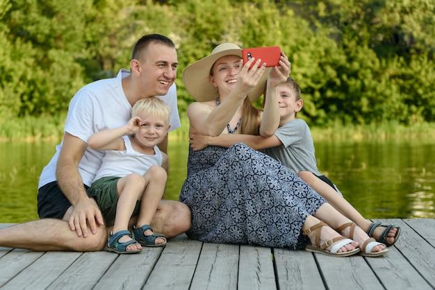 Vater, mutter und zwei kleine söhne sitzen und machen selfies