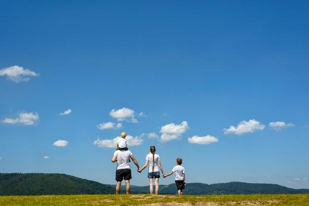 Vater, mutter und zwei kleine söhne stehen auf einer grünen wiese. bewaldete hügel, blauer himmel und wolken. familienwerte
