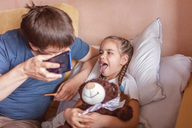 Vater schaut auf den bildschirm des smartphones und berät sich online zu hause mit einem arzt