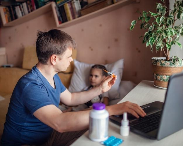 Vater schaut auf laptop-bildschirm und berät sich online zu hause mit einem arzt
