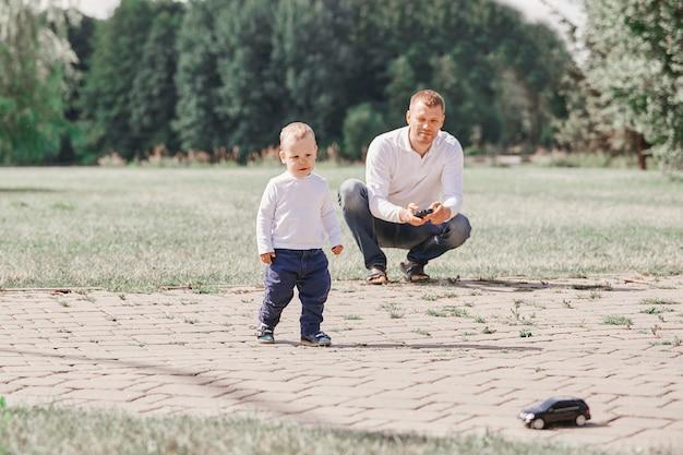 Vater schaut seinen kleinen sohn an, während er im park spazieren geht. das konzept der vaterschaft