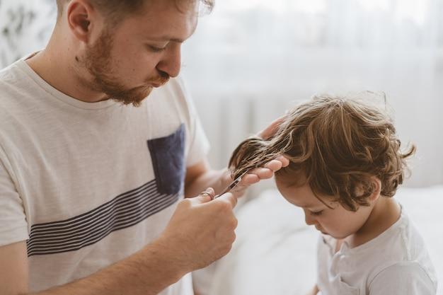 Vater schneidet ihrem sohn im zimmer die haare. familie während der quarantäne