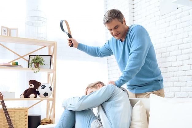 Vater schwingt seinen gürtel, um seinen sohn zu schlagen