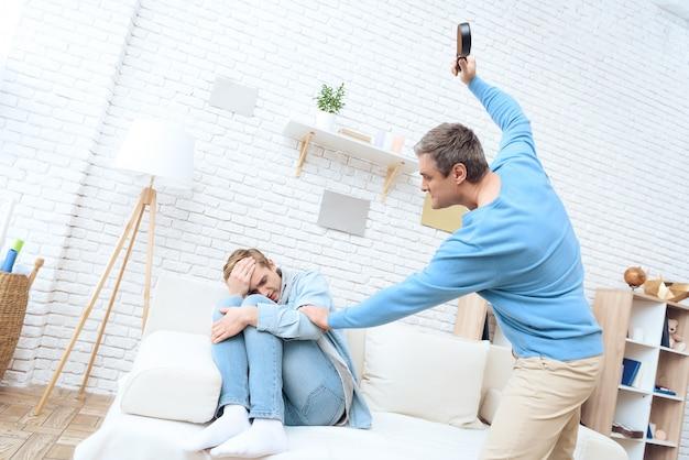 Vater schwingt seinen gürtel, um seinen sohn zu schlagen.