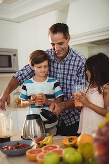 Vater serviert seinen kindern in der küche smoothie