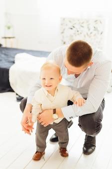 Vater setzte sich neben einen kleinen sohn und umarmt ihn in einem schönen raum
