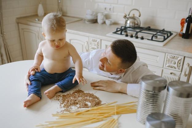 Vater sieht seinen kleinen sohn an, der auf dem tisch sitzt