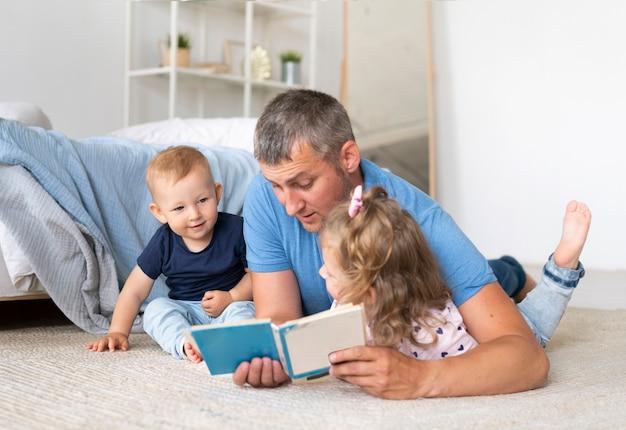 Vater sitzt auf dem boden und liest für kinder