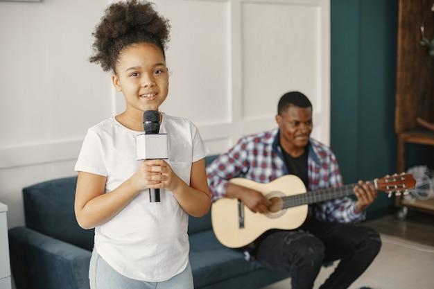 Vater sitzt mit einer gitarre und tochter mit einem mikrofon