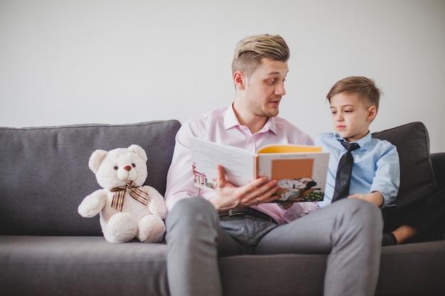 Vater sitzt mit seinem sohn auf dem sofa und liest eine geschichte