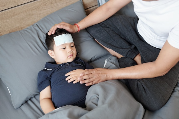 Vater sitzt neben seinem kranken sohn, der im bett mit kühlendem gel auf der stirn ruht und an fieber leidet