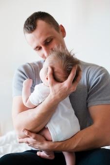 Vater sitzt und umarmt baby