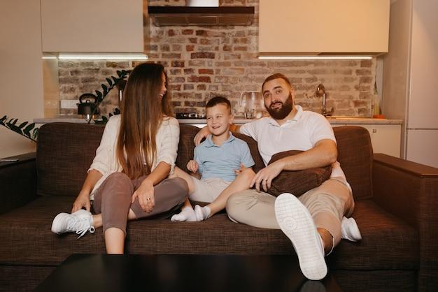 Vater, sohn und mutter schauen mit interesse auf dem sofa in der wohnung fern