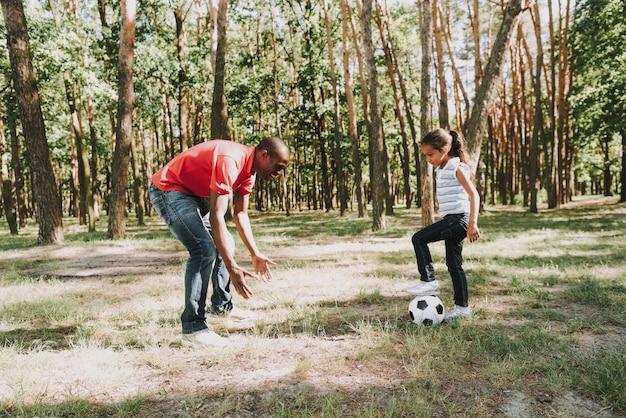 Vater spielt fußball mit tochter, die versucht, ihr den ball abzunehmen.