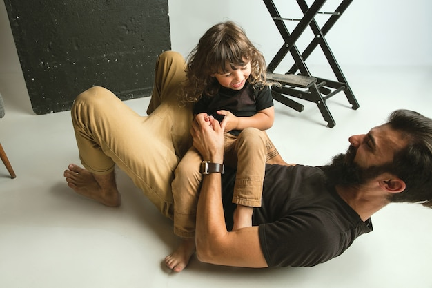Vater spielt mit dem kleinen sohn in ihrem wohnzimmer zu hause. junger vater, der spaß mit seinen kindern in den ferien oder am wochenende hat