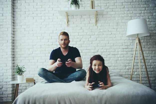 Vater spielt mit seiner kleinen tochter joystick-spiele.