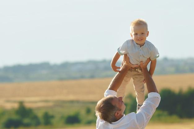 Vater spielt mit sohn auf sommerwiese. familie zu fuß mit kind im freien, exemplar