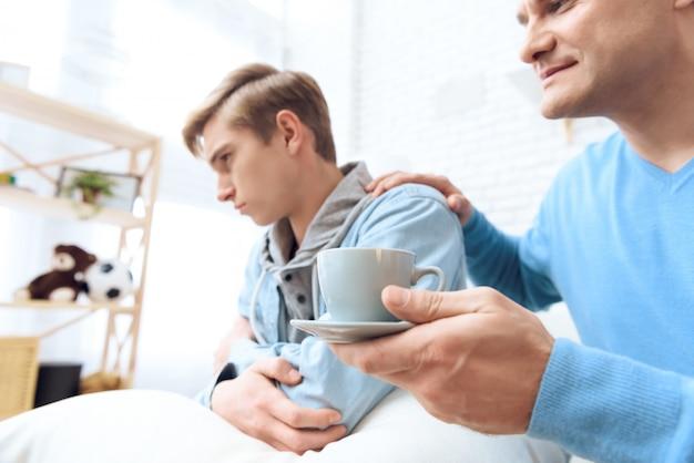 Vater streckt die hand nach dem kaffee aus.