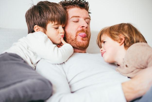 Vater streckt die zunge aus, die mit kind spielt