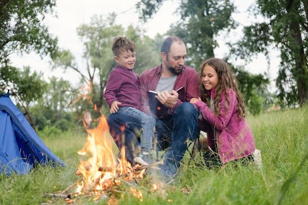 Vater, tochter und sohn sitzen und lesen buch am lagerfeuer im wald. freizeit mit vater, elternschaft. glückliches familienkonzept