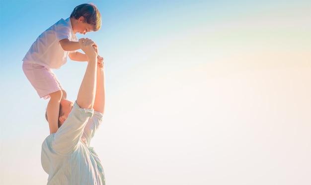 Vater trägt seinen fröhlichen sohn auf seinen schultern mit dem hellen himmel