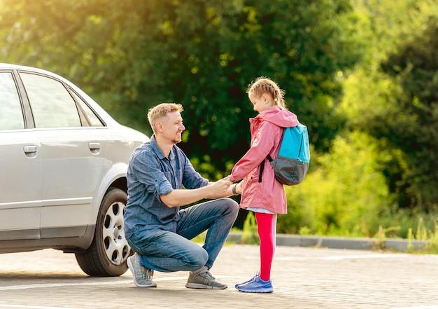 Vater trifft kleines schulmädchen nach dem unterricht auf dem parkplatz