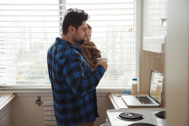 Vater trinkt kaffee, während er sein baby hält