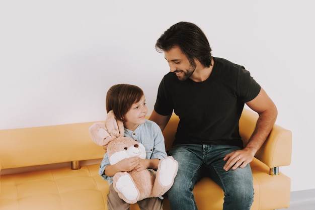 Vater tröstet kind im wartezimmer der kinderklinik