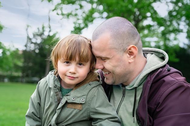Vater umarmt seinen kleinen sohn und lacht. papa und kind verbringen bei frischem sommerwetter zeit zusammen im park. konzept der väterlichen liebe und fürsorge.