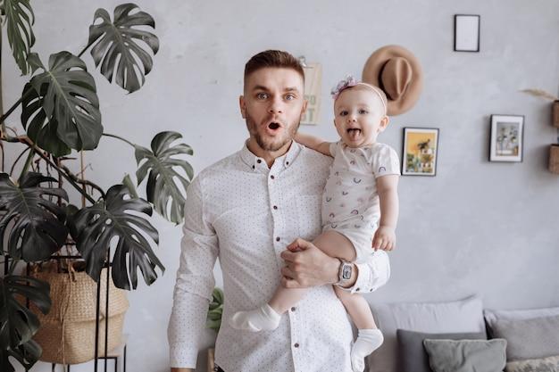 Vater und baby an seinen händen haben spaß zu hause. kleines kind zeigt zunge. glücklicher familientag. vatertag.