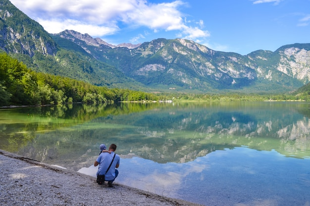 Vater und baby bewundern den ruhigen bergsee an einem strahlend sonnigen tag. mann umarmt sohn auf einer seebirke und schaut in die ferne.