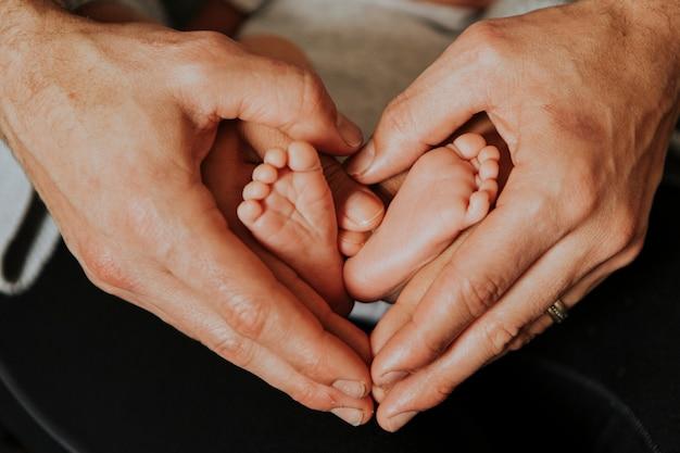 Vater und baby, die eine herzform bilden