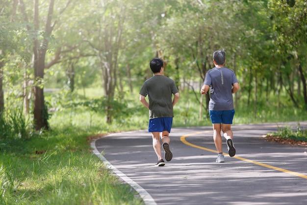 Vater und erwachsener sohn joggen auf dem parkweg