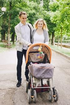 Vater und junge mutter, die ihr baby durch den park in einem wagen zu fuß