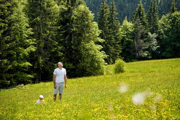 Vater und junger sohn, die auf eine grüne wiese, grüne kiefernwälder gehen.