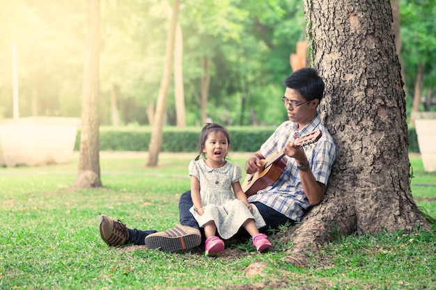 Vater und kind, die spaß haben, gitarre zusammen im park zu spielen