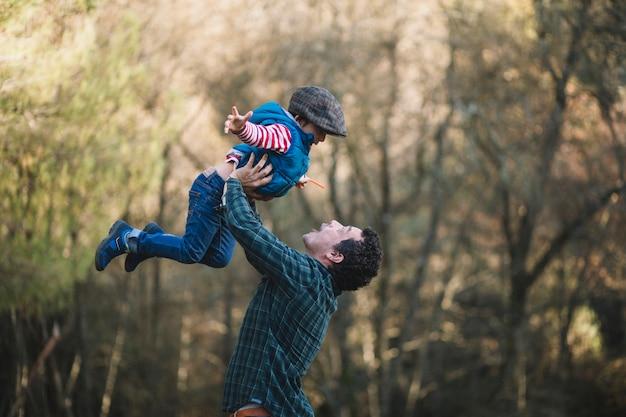 Vater und kind, die spaß im wald haben