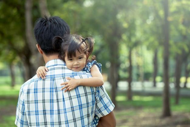 Vater und kind, glückliches kleines mädchen, das auf der schulter ihres vaters im park, weinlesefiltereffekt stillsteht