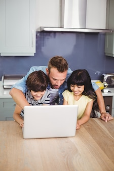 Vater und kinder, die einen laptop verwenden