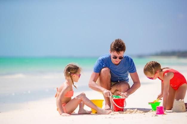 Vater und kinder, die sandburg am tropischen strand machen. familie, die mit strandspielwaren spielt