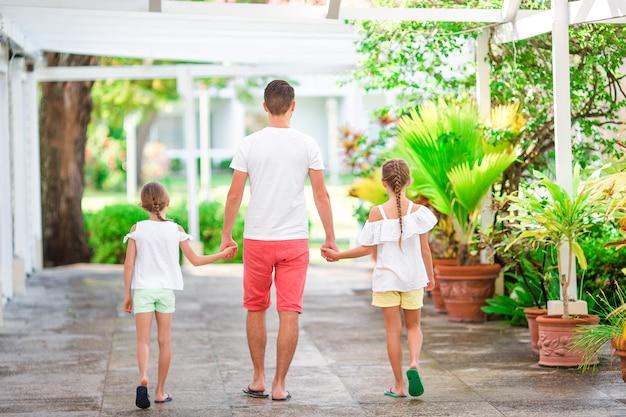 Vater und kinder, die tropische ferien des strandsommers genießen