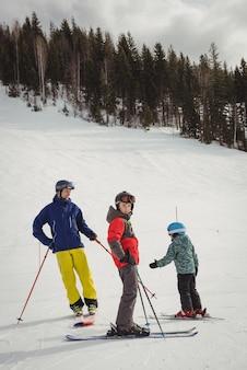 Vater und kinder fahren auf schneebedeckten alpen ski