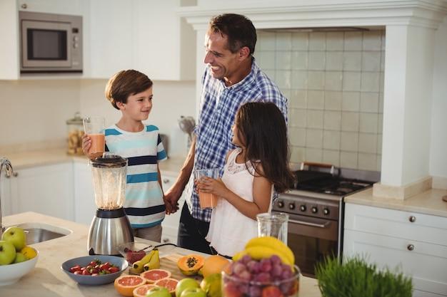 Vater und kinder halten glas smoothie