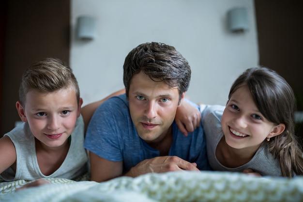 Vater und kinder liegen im schlafzimmer