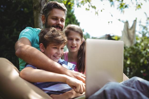 Vater und kinder mit laptop im garten