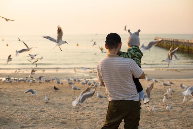 Vater und kleiner sohn füttern möwen am sonnenuntergangsstrand in dubai. mann mit jungen füttern vögel am strand
