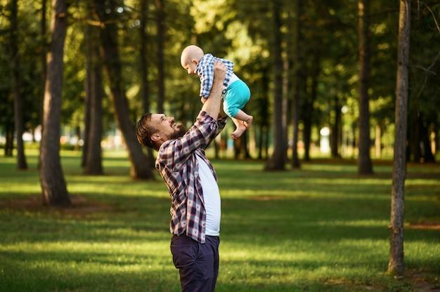 Vater und kleines baby gehen im sommerpark spazieren