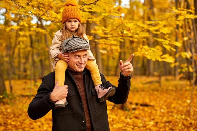 Vater und kleines mädchen gehen im wald, umgeben von gelben und orangefarbenen blättern