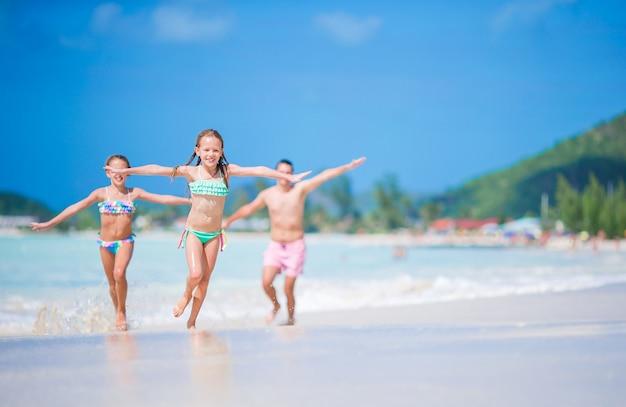 Vater und kleinkinder, die tropische ferien des strandsommers genießen. familie am strand spielen