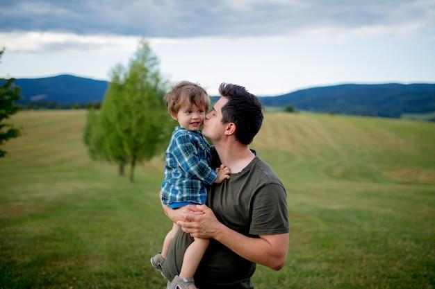Vater- und kleinkindjunge haben spaß in berge